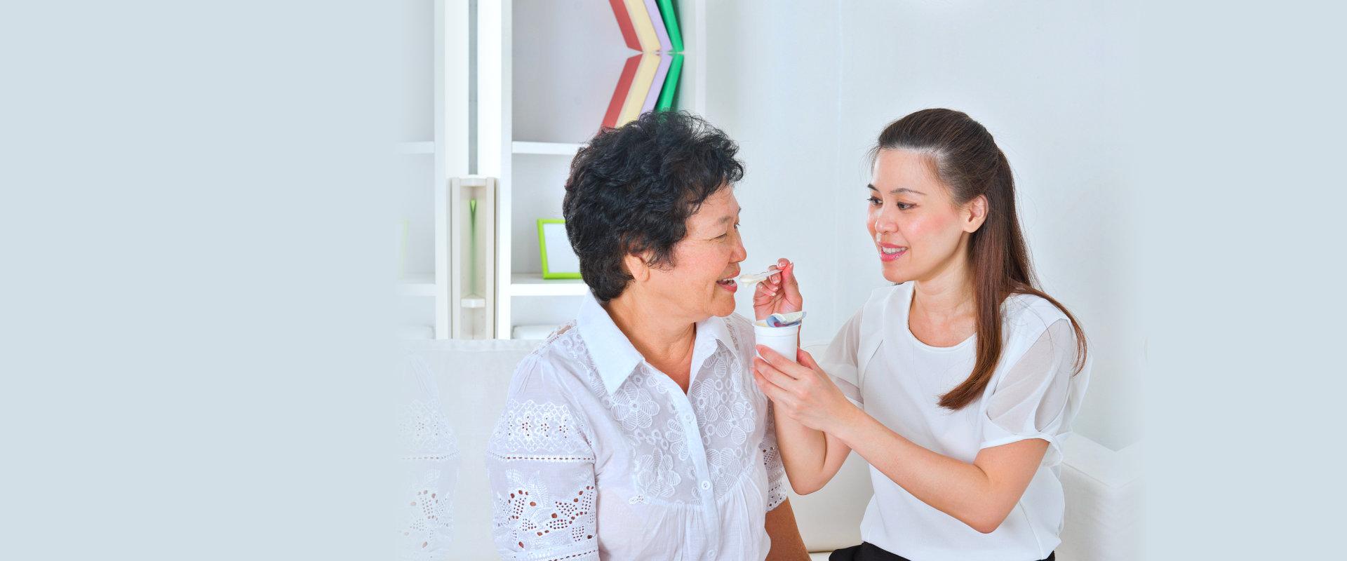 caregiver feeding elderly patient