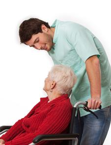 caregiver assisting senior woman in the wheelchair