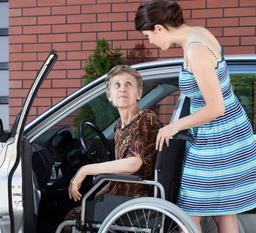 woman assisting old woman to go inside the car