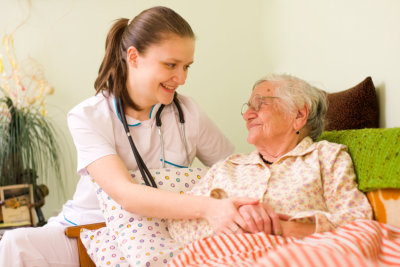 elderly woman in bed with caregiver