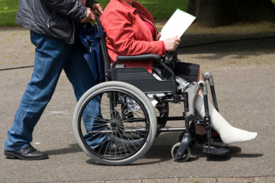 caregivers assisting senior woman in wheelchair
